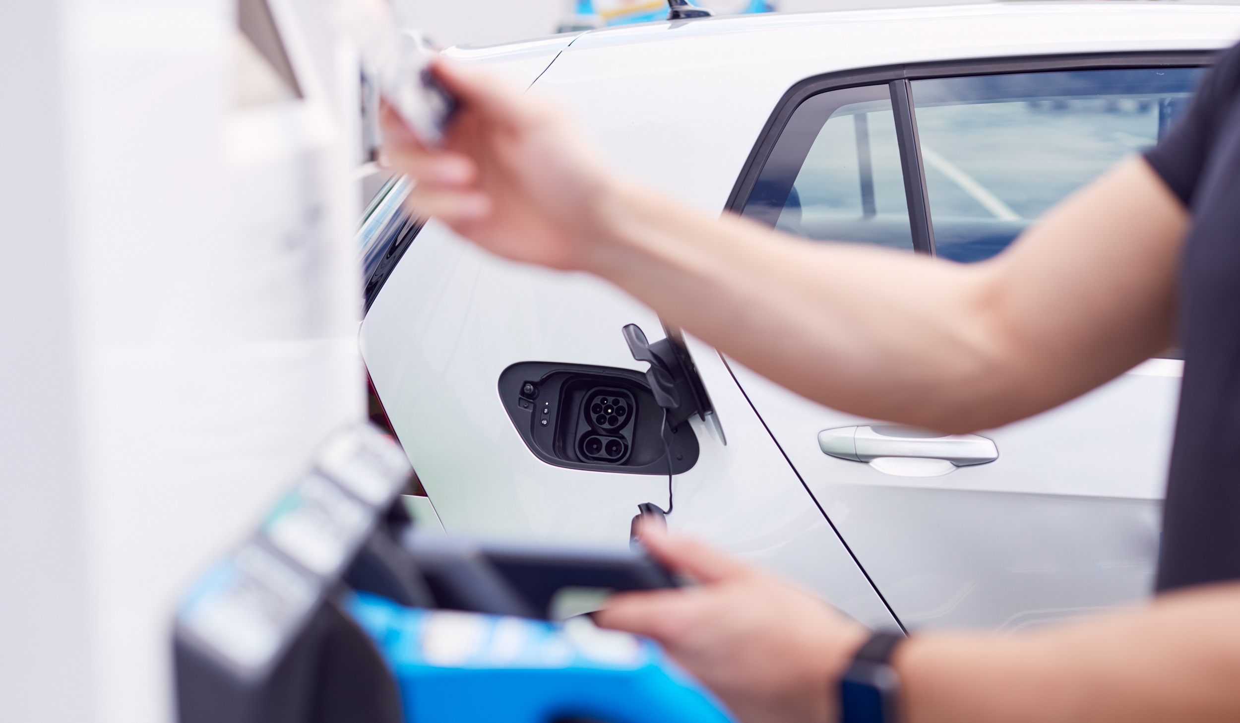 Man Charging Electric Vehicle Paying For Energy With Credit Card At Charging Station